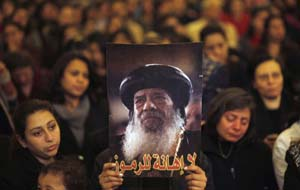 Mourners hold up a picture of Pope Shenouda III, who has died.
